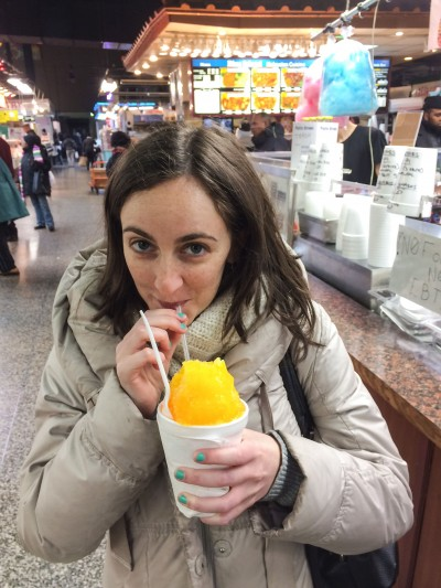Drinking from a yellow pina colada flavored snowcone in Lexington Market