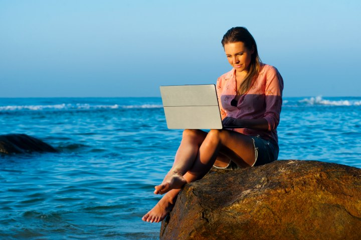 Digital nomad with laptop by ocean