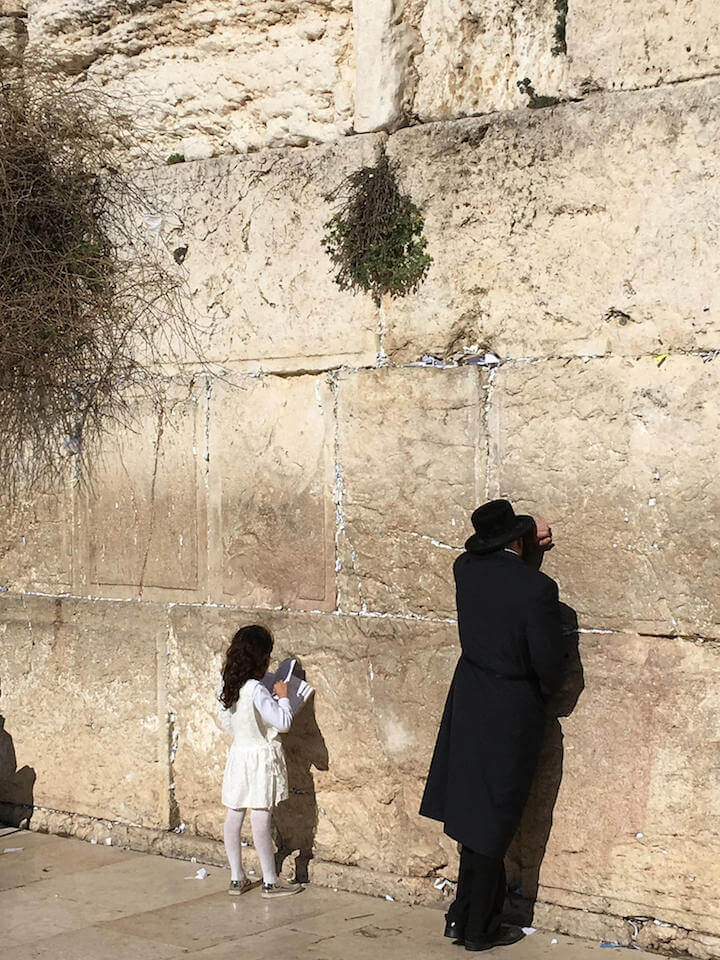 Orthodox Jewish man and little girl praying at the Western Wall