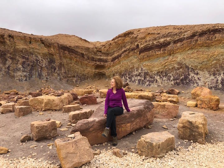 Mom sitting amongst the strata in the Makhtesh Ramon in Israel