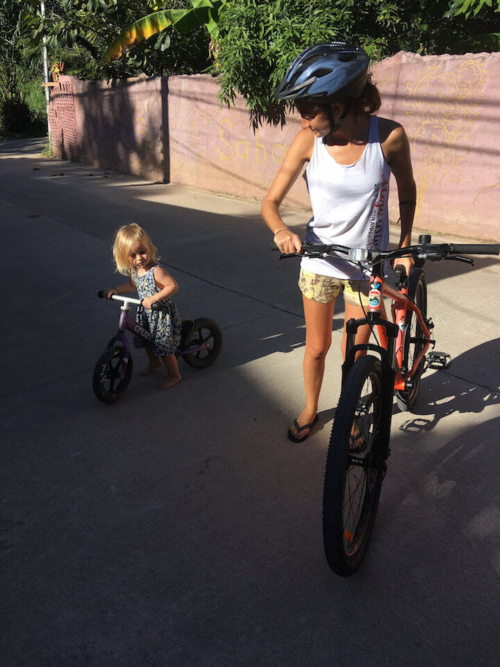 Adult and child learning to ride bicycles together