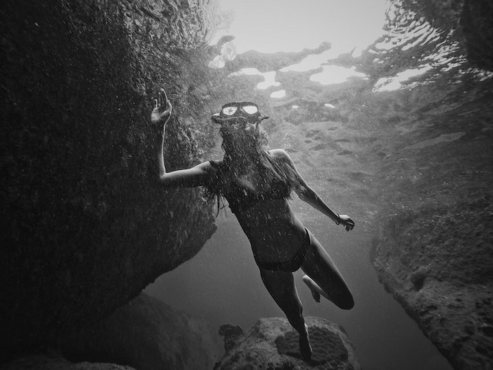 Freediving woman looking up from underwater in Koh Tao in black and white photo