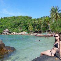 Girl in black bikini sitting on rock at Sai Nuan beach in Koh Tao, Thailand