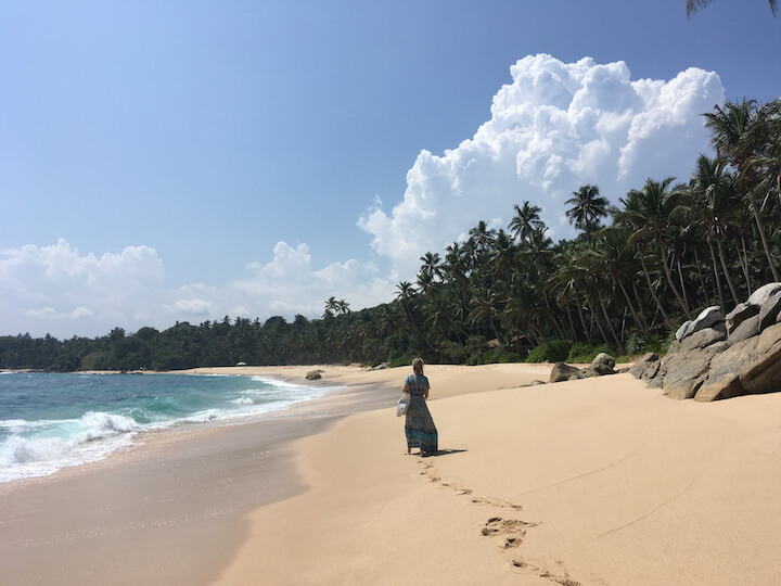 Girl walking on empty beach in Sri Lanka