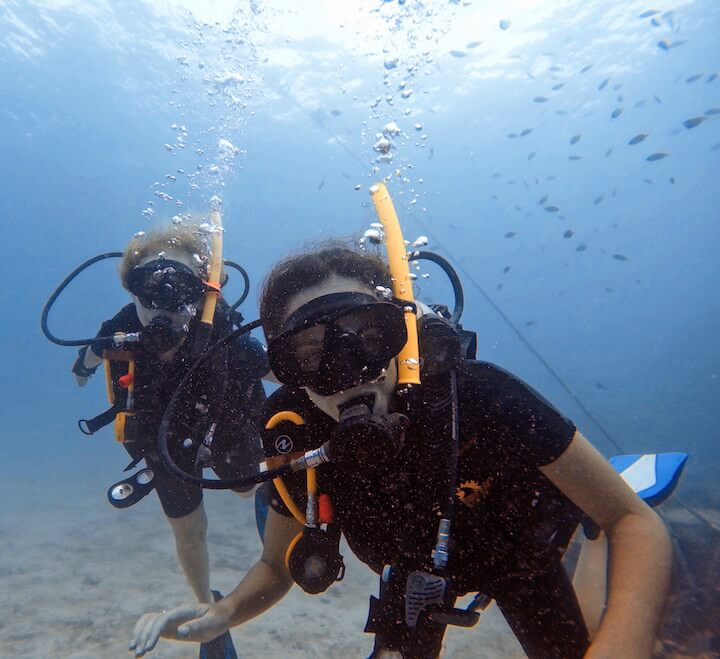 Mom and daughter scuba diving underwater in Koh Tao