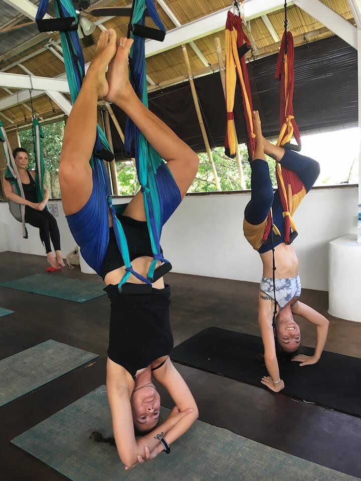 Two girls hanging upside down in aerial yoga class in Canggu, Bali