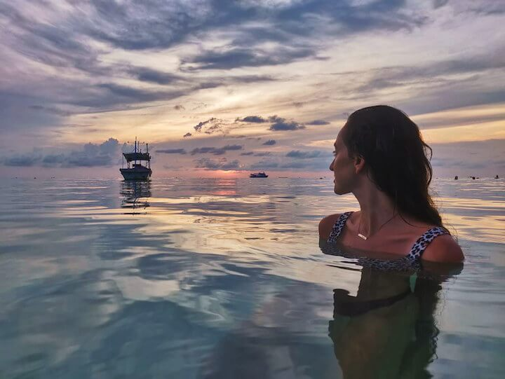 Girl in calm sea reflecting sunset