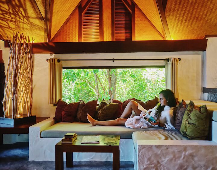 Girl reclining on sofa and reading at The Place Koh Tao luxury pool villa