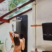 Girl showering in rain shower at The Place Koh Tao