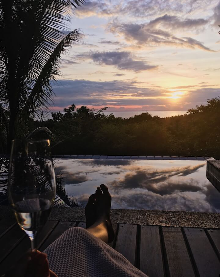 Foot selfie of view of pool, sea, and sunset at The Place Koh Tao