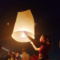 Woman letting go of lantern at Loi Krathong light festival in Chiang Mai Thailand