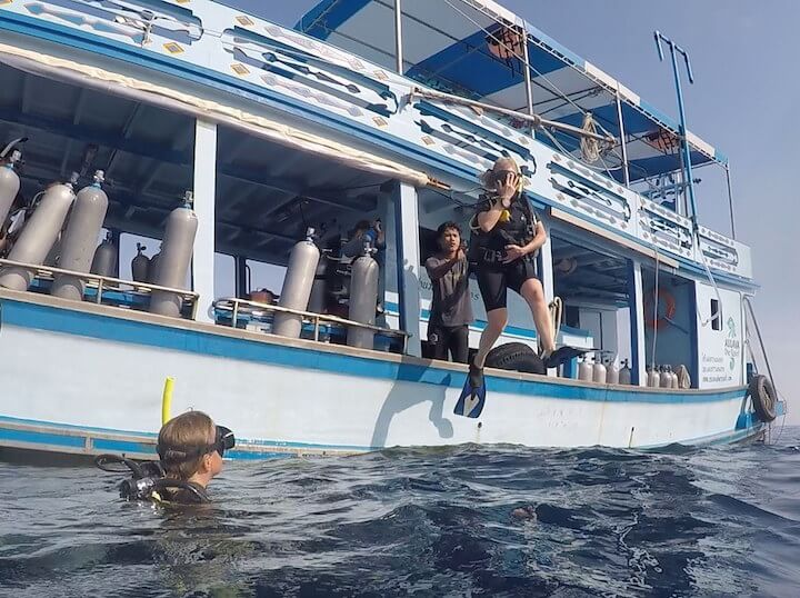 Comparing international health insurance for times like these: Woman scuba diver jumping into ocean