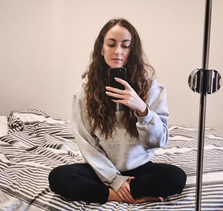 Girl sitting on bed mirror selfie during quarantine